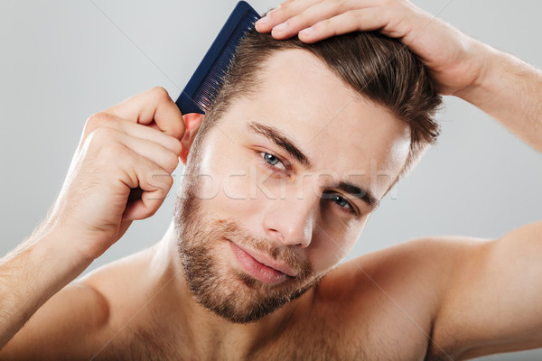 Close up portrait of a smiling man combing his hair Stock photo © deandrobot