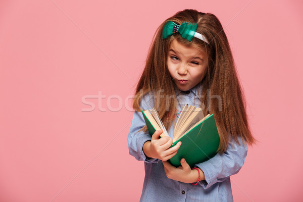 Funny female child with book in hand making faces and fooling ar Stock photo © deandrobot