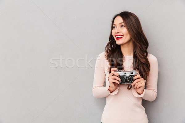 Image of cheerful brunette with red lips in casual holding retro Stock photo © deandrobot