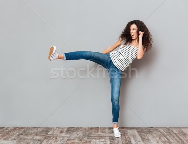 Portrait of strong young female with curly brown hair kicking in Stock photo © deandrobot