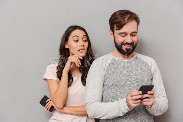Portrait of a young couple using mobile phones Stock photo © deandrobot