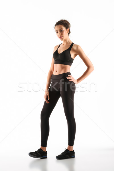Full-length image of Smiling fitness woman holding arm on hip Stock photo © deandrobot