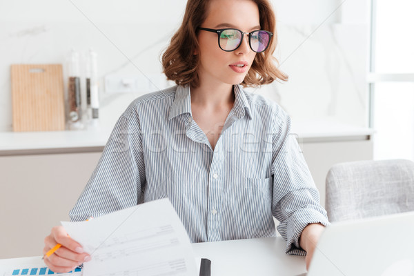 Stock photo: Close-up photo of beautiful thoughtful woman in glasses and stri