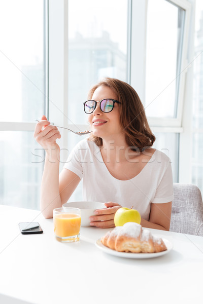 Cheerful young pretty woman eating corn flakes Stock photo © deandrobot