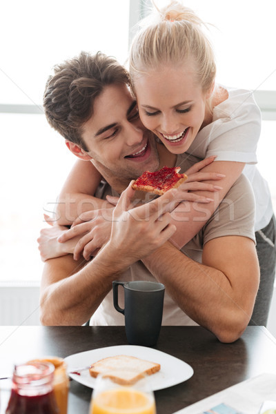 Young funny man feed his lady with bread and jam while have breakfast Stock photo © deandrobot