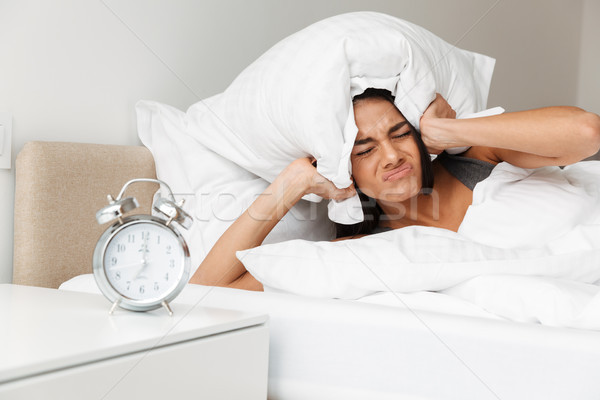 Portrait of caucasian upset woman shutting ears with pillow due  Stock photo © deandrobot