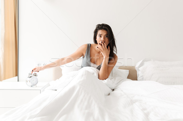 Image of disappointed woman 20s turning off ringing alarm clock  Stock photo © deandrobot