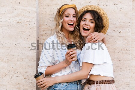 Image of thrilled couple 20s in denim clothing smiling while sit Stock photo © deandrobot