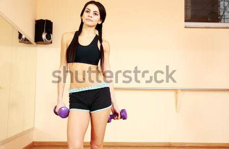 Young smiling fit woman working out with gymnastic stick at gym Stock photo © deandrobot