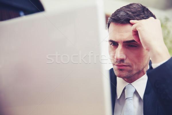 Confident businessman using laptop at office Stock photo © deandrobot