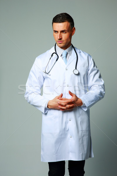 Portrait of a pensive male doctor on gray background Stock photo © deandrobot