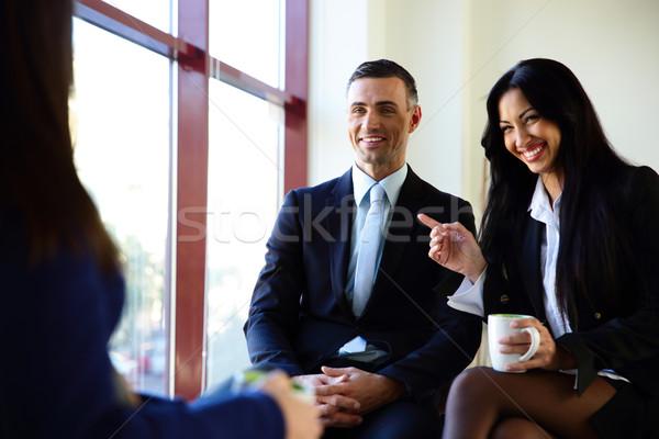 Stock photo: Smiling businesspeople having coffee break in office
