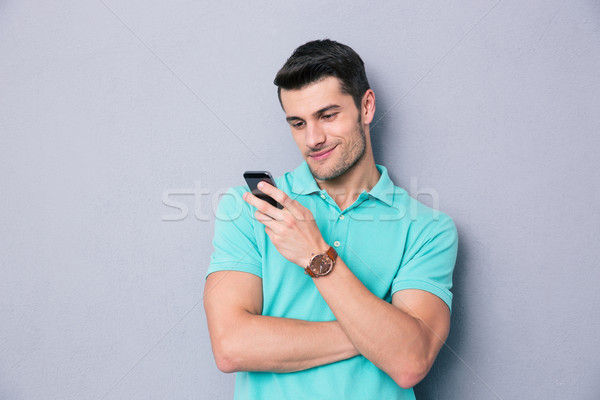 Stock photo: Happy young man using smartphone