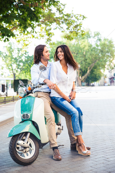 Happy young couple on scooter Stock photo © deandrobot
