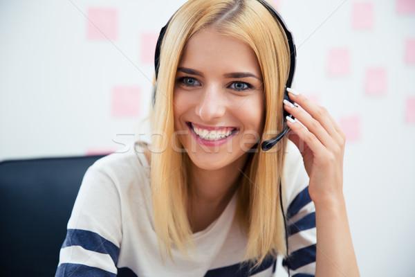 улыбаясь красивая девушка гарнитура сидят таблице служба Сток-фото © deandrobot
