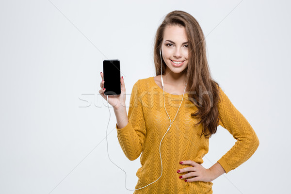 Woman showing blank smartphone screen Stock photo © deandrobot