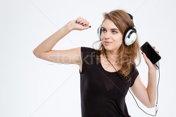 Woman listening the music in headphones Stock photo © deandrobot