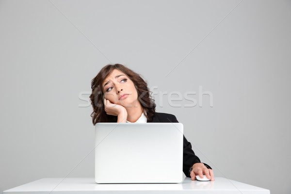 Thoughtful sad business woman dreaming sitting at the laptop Stock photo © deandrobot