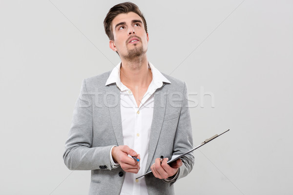 Young man thinking holding clipboard Stock photo © deandrobot