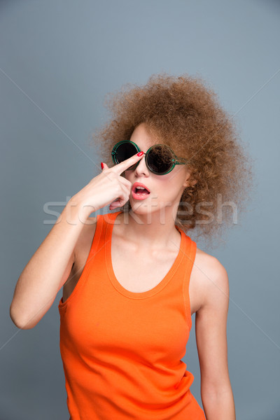 Amusing pretty curly female posing and fixing sunglasses Stock photo © deandrobot