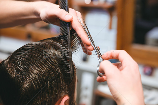 Barbers hands making haircut to man using comb and scissors Stock photo © deandrobot