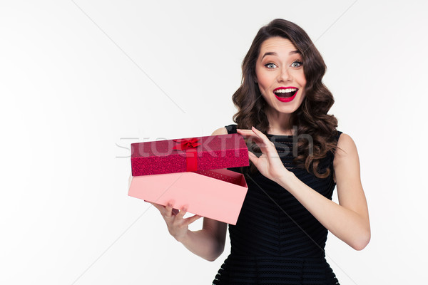 Excited cheerful attractive young woman with retro hairstyle  opening gift  Stock photo © deandrobot