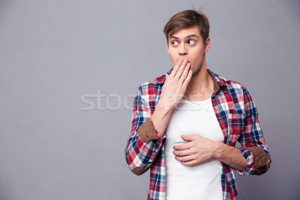 Amazed astonished man covered mouth by hand and feeling afraid Stock photo © deandrobot