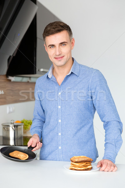 Smiling attractive man cooking and making pancakes  Stock photo © deandrobot
