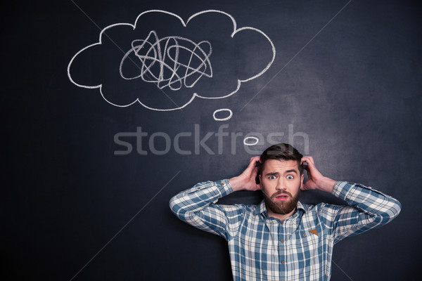 Confused man thinking about problem with black board behind him Stock photo © deandrobot