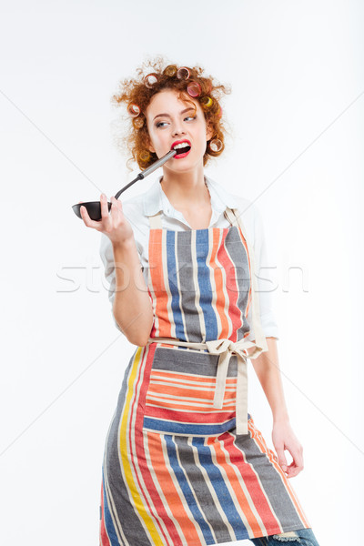 Attractive housewife with curlers in kitchen apron holding soup ladle  Stock photo © deandrobot