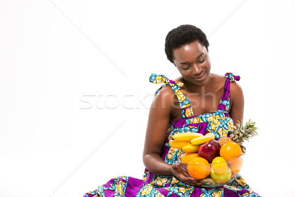 Pretty happy african woman sitting and looking at fresh fruits  Stock photo © deandrobot