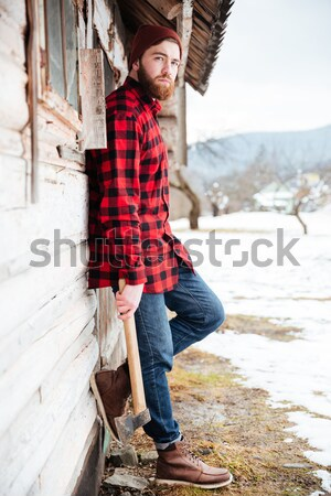 Cheerful man with axe standing near old house in village Stock photo © deandrobot