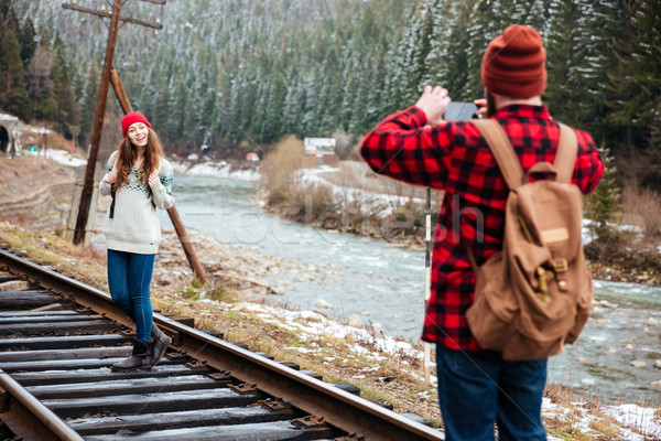 Young man taking photos of girlfriend on railway track  Stock photo © deandrobot