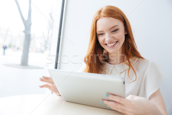 Cheerful woman smiling and using tablet in cafe Stock photo © deandrobot