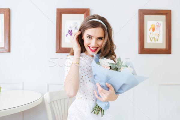 Derűs gyönyörű fiatal nő tart virágcsokor virágok Stock fotó © deandrobot