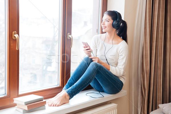 Stockfoto: Vrouw · vergadering · vensterbank · luisteren · muziek · hoofdtelefoon