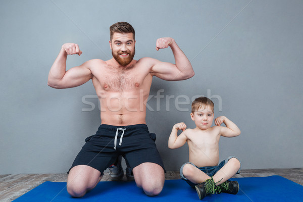 Cheerful father and his little son showing biceps Stock photo © deandrobot