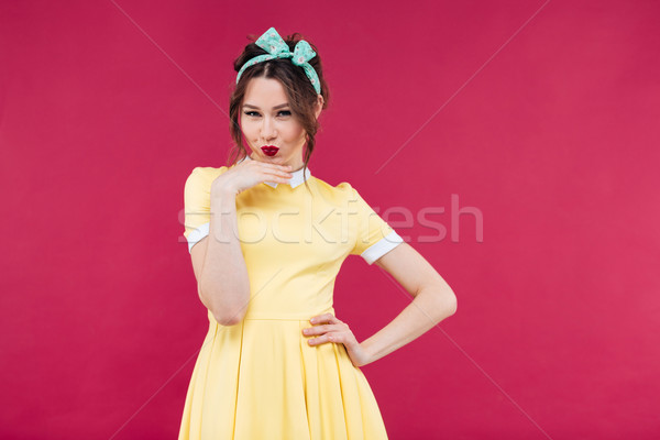 Happy thoughtful pinup girl in yellow dress standing and posing Stock photo © deandrobot