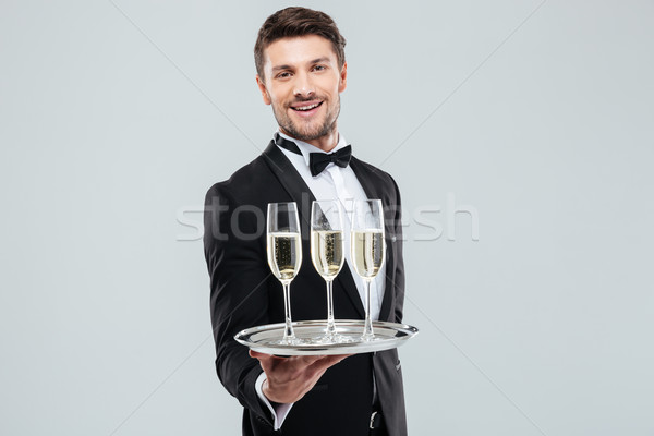 Cheerful young butler in tuxedo smiling and offering champagne Stock photo © deandrobot