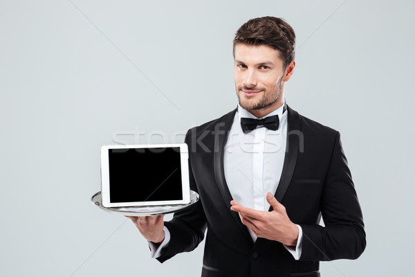 Butler in tuxedo holding and pointing at blank screen tablet Stock photo © deandrobot