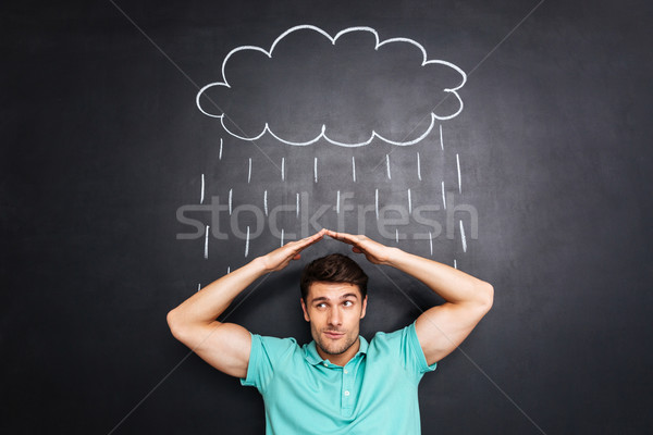 Unhappy young man covering from drawn rain over chalkboard background Stock photo © deandrobot