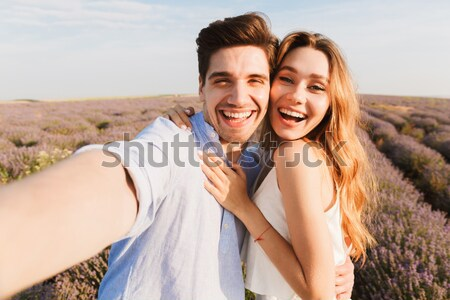 Cheerful married couple standing on the beach Stock photo © deandrobot