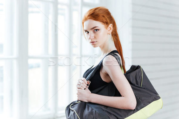 Attractive young woman with bottle of water and sports bag Stock photo © deandrobot