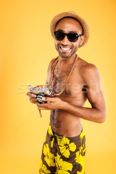 Portrait of a happy afro american man holding photo camera Stock photo © deandrobot
