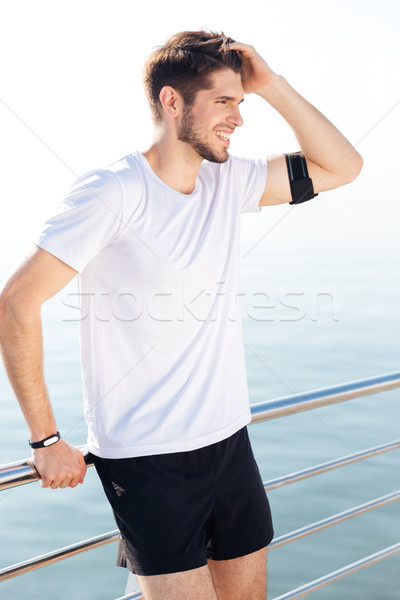 Handsome young sportsman resting at the pier after workout Stock photo © deandrobot