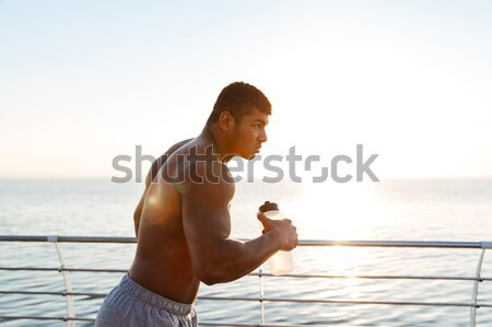 Shirtless african sportsman with bottle of water running on pier Stock photo © deandrobot