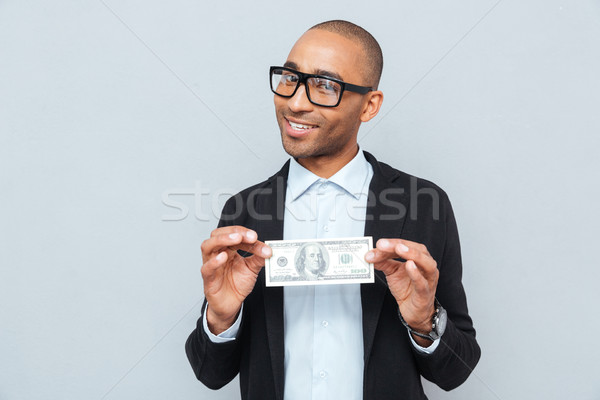 Happy young businessman smiling and holding dollar banknote Stock photo © deandrobot