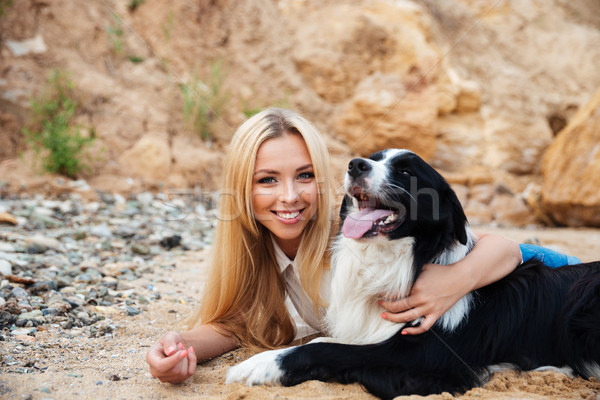 Stock photo: Happy blonde young woman hugging her dog on the beach