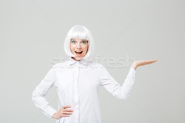 Wondered lovely woman with mouth opened holding copyspace on palm Stock photo © deandrobot