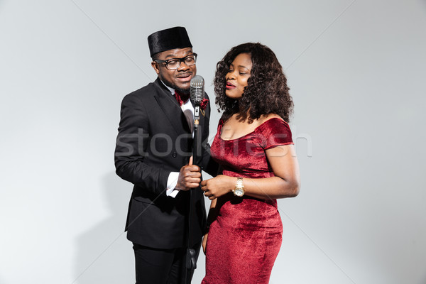 Couple singing into vintage microphone Stock photo © deandrobot